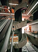 View of escalators and a spiral staircase in a grand shopping mall