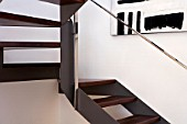 Wooden staircase with painting on wall and stainless steel handrail