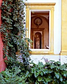 Creepers by old building with statue in background,casa de pilatos,Seville,Spain