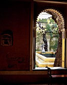 Traditional window with statue in background,casa de pilatos,Seville,Spain