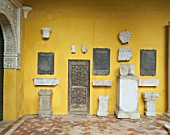 Antiques mounted on painted wall with tile flooring,casa de pilatos,Seville,Spain