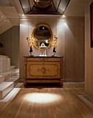 View of an ornate mirror and a wooden cabinet in an illuminated hallway