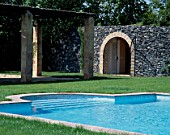 View a clean swimming pool beside a stony wall