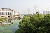 A river polluted with algae flows next to Tiandu Cheng, a Parisian-themed residential development under construction in Hangzhou, China, August 11, 2007.  The development was designed by the Hangzhou Urban planning institute with consultation from Atkins, a British architectural firm.