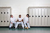 Three men sleeping in locker room
