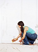 Woman using sandpaper on wall