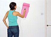 Woman painting a wall pink