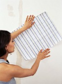 Woman holding up wallpaper sample