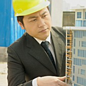 Architect looking at model building