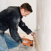A builder attaching a skirting board to a wall