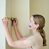Woman measuring a wall