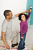 Girl and father painting a wall