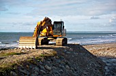 Digger on the beach at Aberdesach, North West Wales.