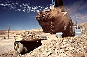 Large digger loading rock and ore on to a truck in an open cast diamond mine, Botswana, Africa