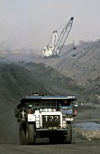 A truck removes coal while Dragline - which is the huge crane like machine  working in the background, South Africa, Middleburg, 2002