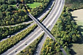Bridge, sliproads and motorway, UK, aerial view