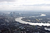 Aerial view of Docklands, Canary Wharf, Isle of Dogs in the mid distance with the sweep of the River Thames in foreground, London, UK
