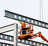 Construction workers guide a steel girder being lowered into place, during construction of a multi-storey car park next to Preston Rail Station, for Network Rail.