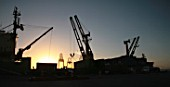Ship And Harbor Crane Silhoueted By Sunset In San Antonio, Chile