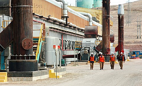 Four workers walking outside electrowinning plant Escondida Chile
