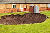 A massive hole opens up in a back garden in Egremont Cumbria as a result of mining subsidence when in June 2005 an old mine shaft opened up