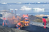 Laying tarmac on a road in Ilulissat on Greenland with icebergs from the Jacobshavn icefjord behind