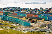 Colourful houses in Illulisat on Greenland. Ilulissat is a UNESCO World Heritage Site because of the Jacobshavn Glacier or Sermeq Kujalleq which is the largest glacier outside Antarctica. The glacier drains 7% of the Greenland ice sheet and produces enough water from calving icebergs in one day to provide New York with water for 1 year. Climate change has meant the glacier has speeded up and is now one of the fastest glaciers in the world at up to 40 metres per day and is also receeding rapidly