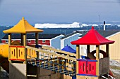 Childrens play ground in Ilulissat on Greenland with icebergs from the Jacobshavn icefjord behind