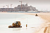 Workers creating a new beach resort on the Palm development in Dubai. Creating new sea front real estate is a questionable thing to do as climate change driven sea level rise could well threaten it in the near future.