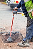 A British Gas worker using a compressed air soil picker to loosen soil around utility pipes as part of a gas pipe replacement upgrade. Since introducing the soil pickers, pipe ruptures have reduced by over 60%