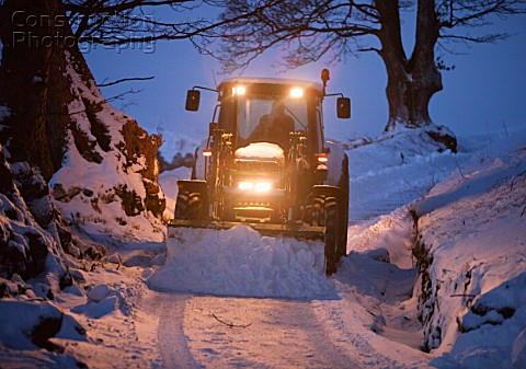 A farmer clearing snow from a lane near Ambleside of snow Lake District UK