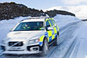 A Police car tries to get over the Kirkstone Pass road above Windermere after it is blocked by spindrift and wind blown snow, Lake District, UK.
