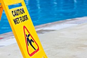 A caution sign on the edge of a swimming pool