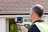A technician uses a thermal imaging camera to check the thermal efficiency of a house, and where heat is lost from the house.