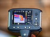 A thermal imaging camera shows heat loss from a hot water pipe.