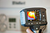A thermal imaging camera shows heat loss from electrical appliances.