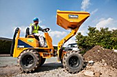 A builder driving a mini dumper truck on a house extension, building job, Ambleside, Cumbria, UK.