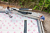 Builders lay under floor insulation into a house extension in Ambleside, UK.
