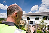 A technician uses a thermal imaging camera to check heat loss from a house.