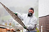 A specialist asbestos removal company removing asbestos from a shed roof of a house in Ambleside, Cumbria, UK.