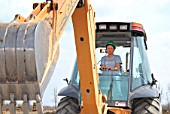 Woman operating backhoe excavator at training facility, Prescott, Ontario, Canada
