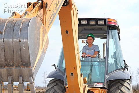 Woman operating backhoe excavator at training facility Prescott Ontario Canada