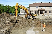 Excavator, digging at residential development, in progress, Ottawa, Ontario, Canada
