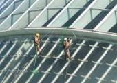 14 October 2009 - Valencia, Spain - Maintenance workers equipped with climbing gear are cleaning the glass facade of the Hemisferic (The white building in the background is the Palau de les Arts Reina Sofia). The Buildings are part of spanish architect Santiago Calatravas Ciudad de les Arts i Ciences/Ciudad de los Artes y Ciencias (City of the Arts and Sciences), a site comprising several edifices that he designed, located in the former bed of the Turia river, in Valencia.