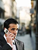 Young businessman using mobile phone in street, close-up