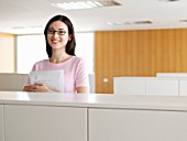 Young businesswoman holding file in office, smiling, portrait
