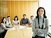 Businesswoman in meeting room, portrait, colleagues in background