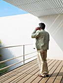 Man standing on balcony using mobile phone, rear view