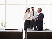 Two businessmen and woman discussing file in office