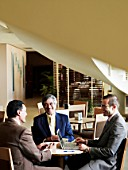 Three businessmen having meeting in restaurant, smiling